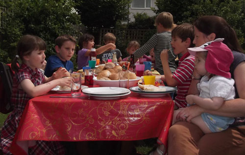Children eating BBQ food at a table in the sunshine.