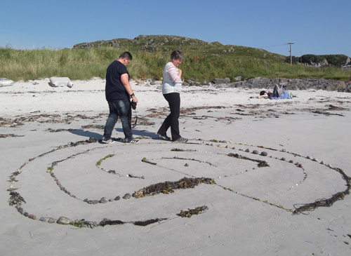 Two women walking aroung a labyrinth on the white sandy beach of Iona.