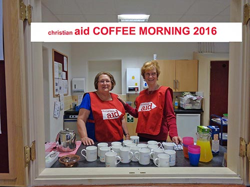Image of Sue and Jenny at the serving hatch with Christian Aid aprons on.
