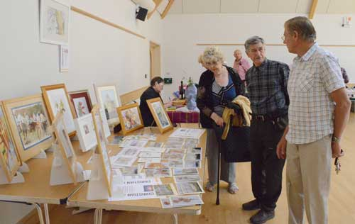 Image of stalls on the morning with pictures painted by the Art group and others.