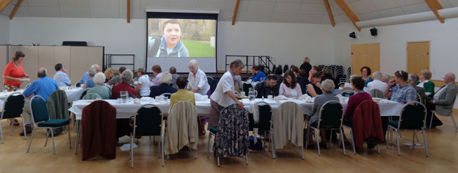 Image of people eating lunch in the Bradbury Hall with a video showing on the large screen.